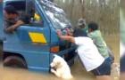 Een hond helpt zijn baasjes om het busje in de stromende regen te duwen: de foto zegt meer dan duizend woorden