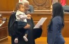 The judge holds a young mother's baby while she takes the oath to become a lawyer