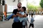 El maestro de educación física toma en brazos a su alumno discapacitado para permitirle de saltar la cuerda