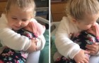 A three-year-old girl holds her little sister in her arms for the first time and instantly feels a strong bond of sisterly love
