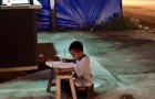 With no electricity at home, this 9-year-old boy does his homework under a street light