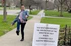 Une femme pose un panneau invitant les passants à