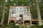 Un couple construit une maison dans les bois avec un mur fait de vieilles fenêtres recyclées