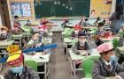 Cina: in questa scuola elementare, gli alunni indossano un cappello largo e colorato per mantenere la distanza di sicurezza
