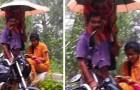 Questo papà regge l'ombrello alla figlia per permetterle di seguire le lezioni online anche sotto la pioggia