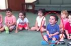 Die Lehrerin beginnt Gitarre zu spielen. Behaltet das Kind in Blau im Auge