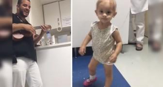 El doctor del reparto de oncologia pediatrica abraza el ukelele y toca para su pequeña paciente