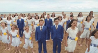Des dizaines d'enfants se rassemblent sur la plage: leur hymne est émouvant