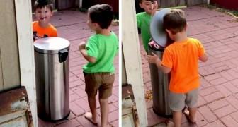 Questi due bimbi si divertono un mondo colpendo il coperchio del bidone della spazzatura con la testa