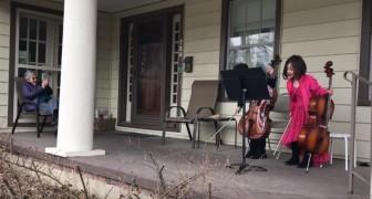 Deux enfants jouent du violoncelle sur le patio d'une voisine âgée pour lui tenir compagnie pendant son confinement