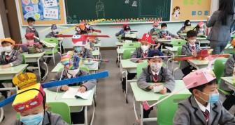 China: Op deze basisschool dragen leerlingen een grote, kleurrijke hoedje om de veiligheidsafstand te bewaren