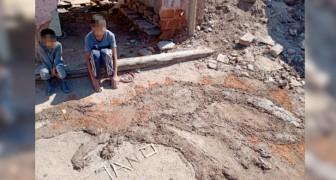 Il n'a pas de papier et de feutres à la maison : un enfant pauvre fait un dessin avec de la terre pour son devoir scolaire