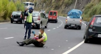 A policeman comforts a 4-year-old boy after a car accident by holding him tightly