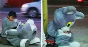 Ein neunjähriger Junge ruht sich als Maskottchen verkleidet am Straßenrand aus: Er unterhält die Autofahrer für ein wenig Geld