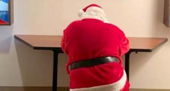 Un uomo vestito da Babbo Natale si inginocchia e prega per i bambini ricoverati in un ospedale pediatrico