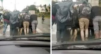 Deutscher Schäferhund steigt aus dem Auto seines Besitzers, das eine Panne hatte, und hilft, es mit anderen Menschen zusammen zu schieben