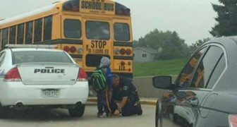 A policeman accompanies a child who had missed the school bus: he didn't want to make him walk alone