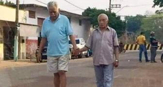 Dos ancianos caminan por la calle de la mano: la imagen de la verdadera amistad