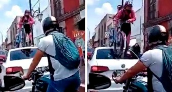 Ein Auto blockiert den Radweg: eine Radfahrerin klettert mit ihrem ganzen Fahrrad darauf, um durchzukommen