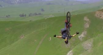 Er fährt mit dem Fahrrad auf einen Hügel. Wenn er abfährt, werdet ihr sprachlos sein.