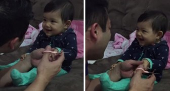 Watch the reaction of this baby, when daddy tries to cut her nails ...