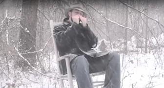 Seduto nella neve, suona un brano con l'armonica: il risultato è POESIA pura