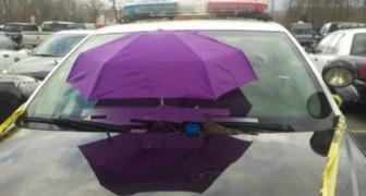 I poliziotti fissano un ombrello sulla macchina... per un motivo decisamente originale