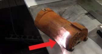 Un fascio laser sfiora un pezzo di metallo arrugginito. L'effetto è un piacere tutto da guardare