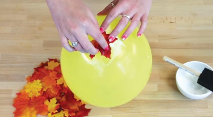 Elle colle des feuilles sur un ballon : ce qu'elle obtient est un objet pour une maison de style automnal !