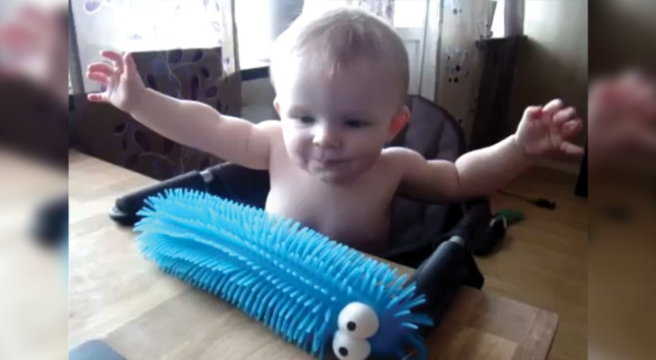 A baby touches a puffer caterpillar toy and is frightened in an adorable way