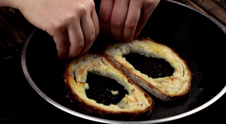 Il troue deux tranches de pain et les met dans la poêle: quand il les remplit, il va créer une recette très curieuse!