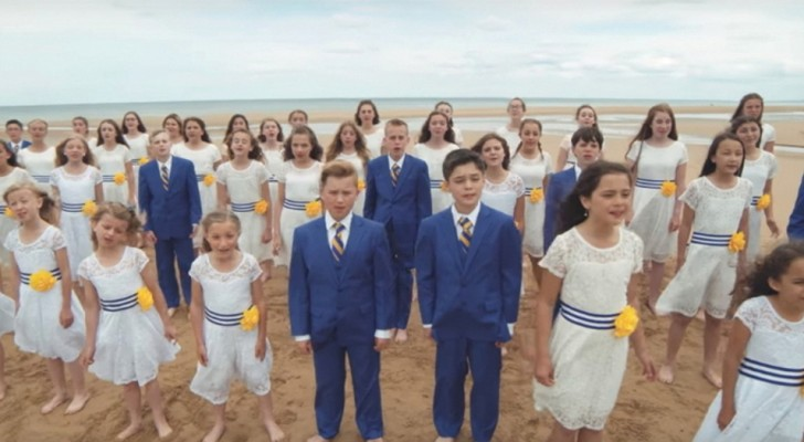 Decine di bambini si radunano sulla spiaggia: il loro tributo canoro è commovente