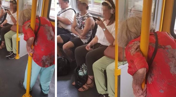 Une dame âgée reste debout dans le train pendant que des jeunes écoutent de la musique, absorbés par leurs téléphones