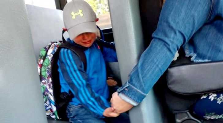 The school bus driver holds the hand of this little boy who is crying on his first day of school
