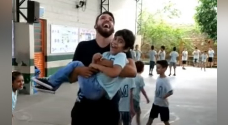 A physical education teacher picks up his disabled student to allow him to experience jumping rope