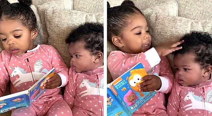 Questa bimba di 2 anni legge una storia alla sua sorellina, imitando quello che fa la mamma