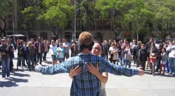 Hij staat midden in een plein vragende om een knuffel, de reacties zijn ontroerend