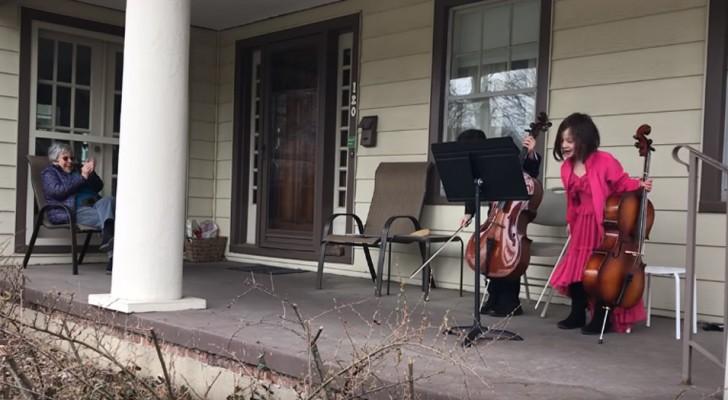 Um einer Nachbarin in häuslicher Isolation eine Freude zu machen, spielen diese Kinder auf der Veranda der alten Dame Cello