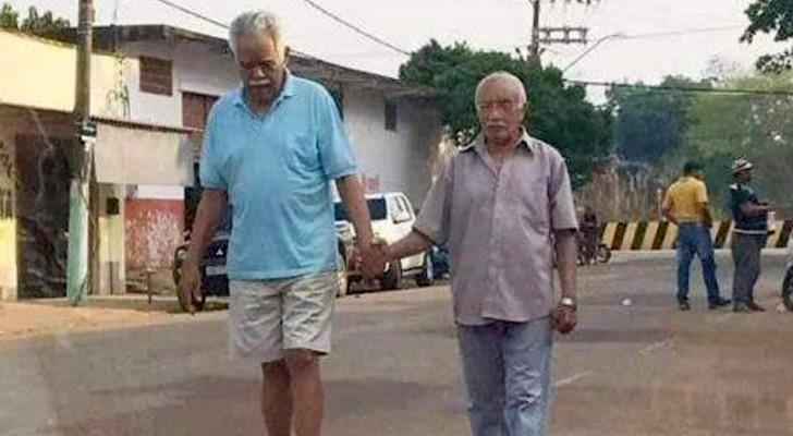 Twee bejaarde mensen lopen hand in hand over straat: het beeld van echte vriendschap