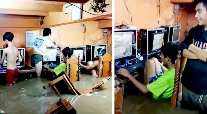 Continuano a giocare ai videogame nonostante il bar viene inondato dall'alluvione, come se nulla fosse