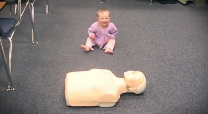 Deze baby weet precies wat er moet gebeuren als er een oefenpop voor haar wordt geplaatst