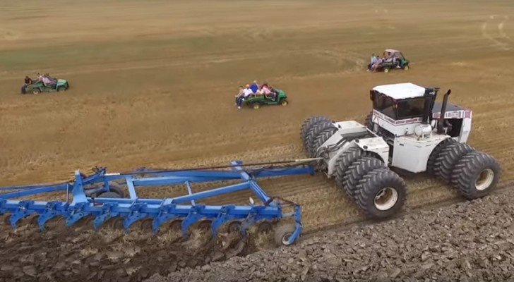 Hier is één van de grootste tractors ter wereld aan het werk... iedereen verzameld zich om het gevaarte te bewonderen