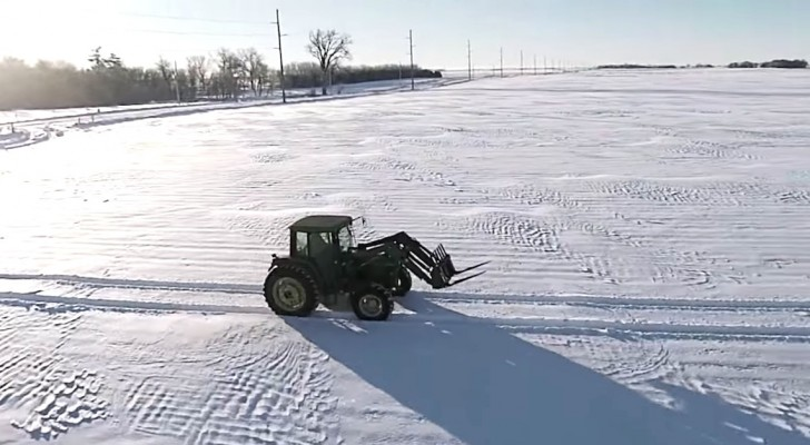 A tractor moves in the snow, but when the camera zooms out ... Wooow!