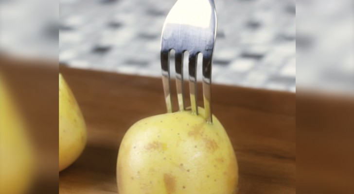 Il embroche une demi-pomme de terre avec une fourchette: voici une astuce utile pour le barbecue!